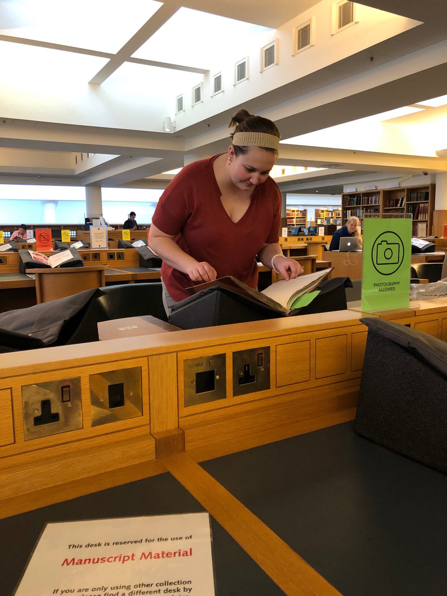A young woman searches through a book in a library.