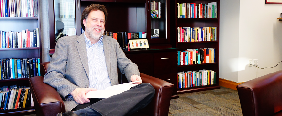 Joe Ward, Dean of the college of humanities and social science, sits smiling before a backdrop of books